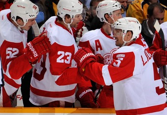 NASHVILLE, TN - DECEMBER 15:   Jonathan Ericsson #53 and Brad Stuart #23 of the Detroit Red Wings congratulate teammate Nicklas Lidstrom #5 on scoring a goal against the Nashville Predators at the Bridgestone Arena on December 15, 2011 in Nashville, Tenne