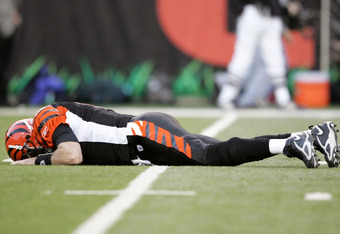 CINCINNATI - JANUARY 08:  Quarterback Carson Palmer #9 of the Cincinnati Bengals lays on the ground after being hit in the knee on the first drive of the AFC Wild Card Playoff Game against the Pittsburgh Steelers at Paul Brown Stadium on January 8, 2006 i