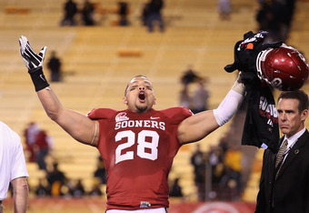 TEMPE, AZ - DECEMBER 30:  Linebacker Travis Lewis #28 of the Oklahoma Sooners celebrates after defeating the Iowa Hawkeyes in the Insight Bowl at Sun Devil Stadium on December 30, 2011 in Tempe, Arizona. The Sooners defeated the Hawkeyes 31-14.  (Photo by