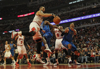 CHICAGO, IL - APRIL 21: Carlos Boozer #5 of the Chicago Bulls grabs a rebound against Ian Mahinmi #28 and Shawn Marion #0 of the Dallas Mavericks at the United Center on April 21, 2012 in Chicago, Illinois. NOTE TO USER: User expressly acknowledges and ag
