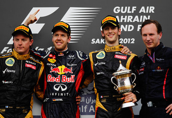 SAKHIR, BAHRAIN - APRIL 22:  Race winner Sebastian Vettel (2nd left) of Germany and Red Bull Racing celebrates on the podium with second placed Kimi Raikkonen (left) of Finland and Lotus, third placed Romain Grosjean (2nd right) of France and Lotus and Re