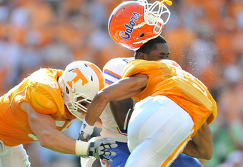 KNOXVILLE, TN - SEPTEMBER 18:  Robert Clark #81 of the Florida Gators loses his helmet after being hit by Jacques Smith #56 and Nick Reveiz #55 of the Tennessee Volunteers during the first half at Neyland Stadium on September 18, 2010 in Knoxville, Tennes