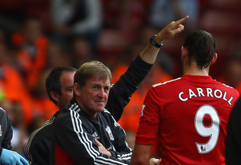 LIVERPOOL, ENGLAND - AUGUST 06:  Andy Carroll of Liverpool with his manager Kenny Dalglish after being substituted during the pre season friendly match between Liverpool and Valencia at Anfield on August 6, 2011 in Liverpool, England.  (Photo by Clive Bru