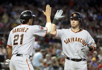 PHOENIX, AZ - APRIL 17:  Buster Posey #28 of the San Francisco Giants high fives teammate Freddy Sanchez #21 after Posey hit a two run home run against the Arizona Diamondbacks during the sixth inning of the Major League Baseball game at Chase Field on Ap
