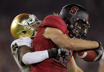 STANFORD, CA - NOVEMBER 26:  Coby Fleener #82 of the Stanford Cardinal is tackled by Jamoris Slaughter #26 of the Notre Dame Fighting Irish at Stanford Stadium on November 26, 2011 in Stanford, California.  (Photo by Ezra Shaw/Getty Images)
