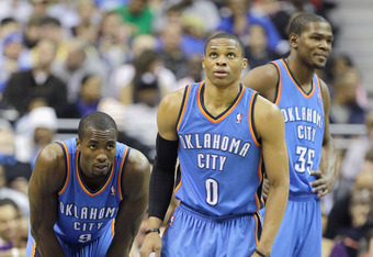 WASHINGTON, DC - MARCH 14: Russell Westbrook #0 of the Oklahoma City Thunder stands with teammates Serge Ibaka #9 and Kevin Durant #35 during the first half against the Washington Wizardsat the Verizon Center on March 14, 2011 in Washington, DC. NOTE TO U