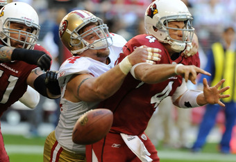GLENDALE, AZ - DECEMBER 11:  Kevin Kolb #4 of the Arizona Cardinals is hit by Justin Smith #94 of the San Francisco 49ers as he tries to thorw the ball down field at University of Phoenix Stadium on December 11, 2011 in Glendale, Arizona.  (Photo by Norm