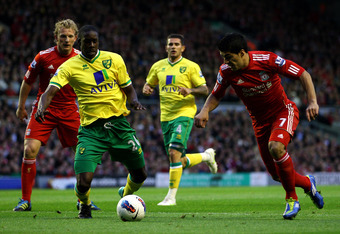 LIVERPOOL, ENGLAND - OCTOBER 22:  Luis Suarez of Liverpool competes with Leon Barnett of Norwich City during the Barclays Premier League match between Liverpool and Norwich City at Anfield on October 22, 2011 in Liverpool, England.  (Photo by Richard Heat