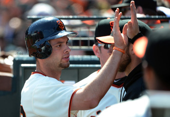 Brandon Belt is congratulated for being allowed to wear a batting helmet.