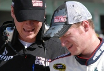 Dale Earnhardt Jr. listens to crew chief Steve Latarte as the sun bothers his eye