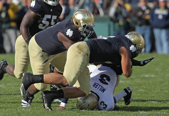 SOUTH BEND, IN - OCTOBER 29: Manti Te'o #5 (R) and Louis Nix III #9 of the Notre Dame Fighting Irish bring down Trey Miller #3 of the Navy Midshipmen at Notre Dame Stadium on October 29, 2011 in South Bend, Indiana. Notre Dame defeated Navy 56-14.  (Photo