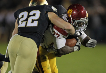SOUTH BEND, IN - OCTOBER 22: Curtis McNeal #22 of the University of Southern California Trojans is hit by Harrison Smith #22 of the Notre Dame Fighting Irish at Notre Dame Stadium on October 22, 2011 in South Bend, Indiana. USC defeated Notre Dame 31-17.