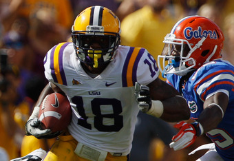 BATON ROUGE, LA - OCTOBER 08:  Brandon Taylor #18 of the Louisiana State University Tigers avoids a tackle after an interception over Frankie Hammond #85 of the Florida Gators at Tiger Stadium on October 8, 2011 in Baton Rouge, Louisiana.   The Tigers def