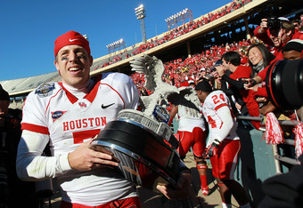 DALLAS, TX - JANUARY 02:  Case Keenum #7 of the Houston Cougars carries the TicketCity Bowl trophy after a 30-14 win against the Penn State Nittany Lions at Cotton Bowl Stadium on January 2, 2012 in Dallas, Texas.  (Photo by Ronald Martinez/Getty Images)