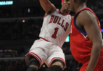 CHICAGO, IL - APRIL 28:  Derrick Rose #1 of the Chicago Bulls grimaces as he goes up to pass over Lavoy Allen #50 of the Philadelphia 76ers after apparently injuring his knee in Game One of the Eastern Conference Quarterfinals during the 2012 NBA Playoffs