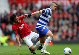 MANCHESTER, ENGLAND - APRIL 08:  Adel Taarabt of Queens Park Rangers tangles with Rafael of Manchester United during the Barclays Premier League match between Manchester United and Queens Park Rangers at Old Trafford on April 8, 2012 in Manchester, Englan