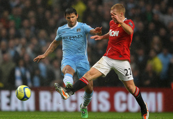 MANCHESTER, ENGLAND - JANUARY 08:  Paul Scholes of Manchester United competes with Sergio Aguero of Manchester City during the FA Cup Third Round match between Manchester City and Manchester United at the Etihad Stadium on January 8, 2012 in Manchester, E