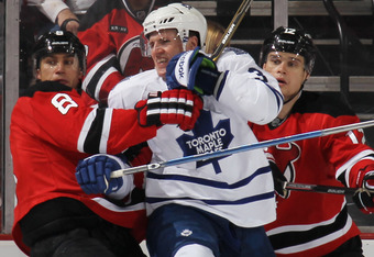 NEWARK, NJ - MARCH 23: Dainius Zubrus #8 of the New Jersey Devils hangs onto Dion Phaneuf #3 of the Toronto Maple Leafs at the Prudential Center on March 23, 2012 in Newark, New Jersey.  The Maple Leafs defeated the Devils 4-3 in the shootout. (Photo by B