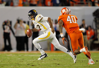 MIAMI GARDENS, FL - JANUARY 04:  Geno Smith #12 of the West Virginia Mountaineers runs with the ball away from pressure by Andre Branch #40 of the Clemson Tigers during the Discover Orange Bowl at Sun Life Stadium on January 4, 2012 in Miami Gardens, Flor