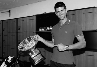 MELBOURNE, AUSTRALIA - JANUARY 29:  (EDITORS NOTE: Image has been converted to black and white. Colour version available.) Novak Djokovic of Serbia poses with the Norman Brookes Challenge Cup in the players locker room after winning the men's final match