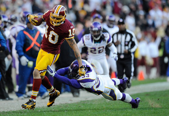 LANDOVER, MD - DECEMBER 24:   Jabar Gaffney #10 of the Washington Redskins breaks the tackle of Jamarca Sanford #33 of the Minnesota Vikings during a game at FedExField on December 24, 2011 in Landover, Maryland.  (Photo by Patrick McDermott/Getty Images)