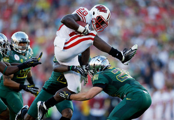 PASADENA, CA - JANUARY 02:  Running back Montee Ball #28 of the Wisconsin Badgers leaps over John Boyett #20 of the Oregon Ducks in the third quarter at the 98th Rose Bowl Game on January 2, 2012 in Pasadena, California.  (Photo by Jeff Gross/Getty Images