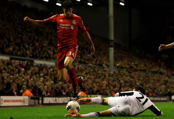 LIVERPOOL, ENGLAND - MAY 01:   Martin Kelly of Liverpool hurdles the challenge of Kerim Frei of Fulham during the Barclays Premier League match between Liverpool and Fulham at Anfield on May 1, 2012 in Liverpool, England. (Photo by Clive Brunskill/Getty I
