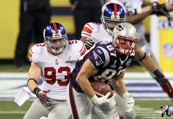 INDIANAPOLIS, IN - FEBRUARY 05:  Rob Gronkowski #87 of the New England Patriots gets tackled by Kenny Phillips #21 and Chase Blackburn #93 of the New York Giants during Super Bowl XLVI at Lucas Oil Stadium on February 5, 2012 in Indianapolis, Indiana.  (P