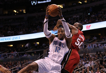 ORLANDO, FL - MARCH 13:  Dwight Howard #12 of the Orlando Magic attempts a shot against Joel Anthony #50 of the Miami Heat during the game at Amway Center on March 13, 2012 in Orlando, Florida.  NOTE TO USER: User expressly acknowledges and agrees that, b