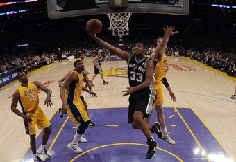 LOS ANGELES, CA - APRIL 17:  Boris Diaw #33 of the San Antonio Spurs scores on a layup past Pau Gasol #16, Andrew Bynum #17 and Metta World Peace #15 of the Los Angeles Lakers during a 112-91 Spurs win at Staples Center on April 17, 2012 in Los Angeles, C