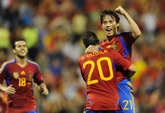 ALICANTE, SPAIN - OCTOBER 11:  David Silva (R) of Spain celebrates scoring his sides second goal with his teammate Santi Cazorla and Pedro Rodriguez (L) during the UEFA EURO 2012 Group I Qualifier between Spain and Scotland at the Rico Perez stadium on Oc