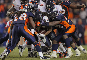 DENVER, CO - DECEMBER 11:  Running back Marion Barber #24 of the Chicago Bears is stopped by Elvis Dumervil #92 and Quinton Carter #28 and the Denver Broncos defense at Sports Authority Field at Mile High on December 11, 2011 in Denver, Colorado. The Bron