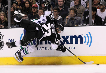 LOS ANGELES, CA - APRIL 15:  Dustin Brown #23 of the Los Angeles Kings and Kevin Bieksa #3 of the Vancouver Canucks collide against the boards in Game Three of the Western Conference Quarterfinals during the 2012 NHL Stanley Cup Playoffs at Staples Center