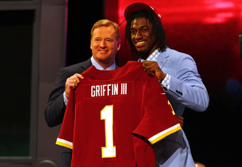 NEW YORK, NY - APRIL 26:  Robert Griffin III (R) from Baylor holds up a jersey as he stands on stage with NFL Commissioner Roger Goodell after Griffin was selected #2 overall by the Washington Redskins in the first round of the 2012 NFL Draft at Radio Cit