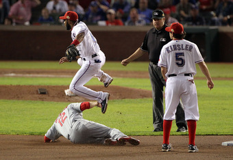 ARLINGTON, TX - OCTOBER 23: Elvis Andrus #1 of the Texas Rangers turns the double play as Lance Berkman #12 of the St. Louis Cardinals slides into second base in the fifth inning during Game Four of the MLB World Series at Rangers Ballpark in Arlington on