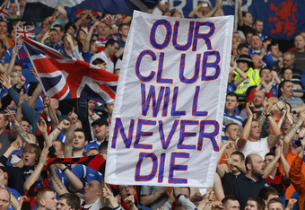 GLASGOW, SCOTLAND - MARCH 25:  Rangers fans hold a banner aloft displaying the message 'our club will never die' during the Clydesdale Bank Scottish Premier League match between Rangers and Celtic at Ibrox Stadium on March 25, 2012 in Glasgow, Scotland.