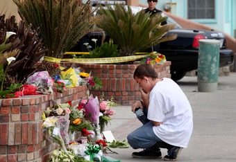 OCEANSIDE, CA - MAY 2:  A wellwisher kneels next to a makeshift shrine in front of Junior Seau's beach home May 2, 2012 in Oceanside, California. Seau, who played for various NFL teams including the San Diego Chargers, Miami Dolphins and New England Patri