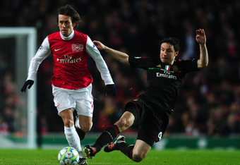 LONDON, ENGLAND - MARCH 06: Mark van Bommel of AC Milan goes in for the tackle on Tomas Rosicky of Arsenal during the UEFA Champions League Round of 16 second leg match between Arsenal and AC Milan at Emirates Stadium on March 6, 2012 in London, England.