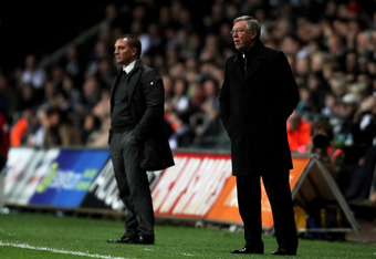SWANSEA, WALES - NOVEMBER 19:  Sir Alex Ferguson (R) the Manchester United manager and Brendan Rogers the Swansea manager look on during the Barclays Premier League match between Swansea City and Manchester United at The Liberty Stadium on November 19, 20