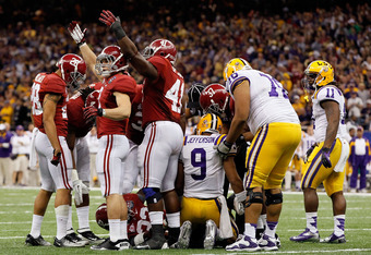 NEW ORLEANS, LA - JANUARY 09:  Vinnie Sunseri #3 and Courtney Upshaw #41 of the Alabama Crimson Tide gestures for help after the injury of teammate C.J. Mosley #32 as Jordan Jefferson #9 and Chris Faulk #76 of the Louisiana State University Tigers look on