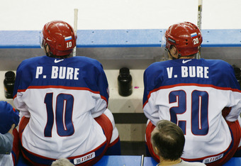 SALT LAKE CITY - FEBRUARY 22:  Pavel Bure #10 and Valeri Bure #20 of Russia look on from the bench as the USA celebrates their win in the men's ice hockey semifinal during the Salt Lake City Winter Olympic Games at the E Center in Salt Lake City, Utah.  U