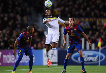 BARCELONA, SPAIN - APRIL 24:  Didier Drogba of Chelsea (C) controls a duels for a high ball with under a challenge by Dani Alves (L) and Sergio Busquets of FC Barcelona during the UEFA Champions League Semi Final, second leg match between FC Barcelona and
