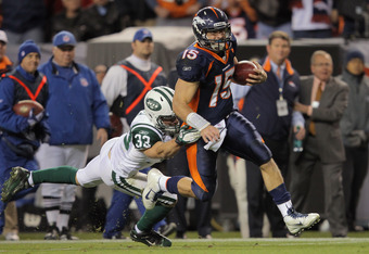 DENVER, CO - NOVEMBER 17:  Quarterback Tim Tebow #15 of the Denver Broncos eludes Eric Smith #33 of the New York Jets and rushes 20 yards for the game winning touchdown in the fourth quarter at Sports Authority Field at Mile High on November 17, 2011 in D