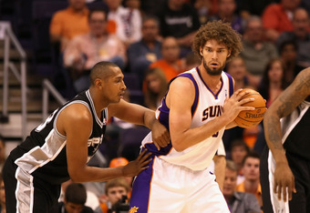PHOENIX, AZ - MARCH 27:  Robin Lopez #15 of the Phoenix Suns handles the ball during the NBA game against the San Antonio Spurs at US Airways Center on March 27, 2012 in Phoenix, Arizona. The Spurs defeated the Suns 107-100. NOTE TO USER: User expressly a