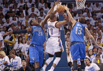 OKLAHOMA CITY, OK - APRIL 30:  Russell Westbrook #0 of the Oklahoma City Thunder shoots under pressure from Delonte West #13 and Ian Mahinmi #28 of the Dallas Mavericks in Game Two of the Western Conference Quarterfinals in the 2012 NBA Playoffs on April