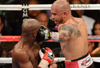 LAS VEGAS, NV - MAY 05:  (R-L) Miguel Cotto connects with a left to the face of Floyd Mayweather Jr. fight during their WBA super welterweight title fight at the MGM Grand Garden Arena on May 5, 2012 in Las Vegas, Nevada.  (Photo by Ethan Miller/Getty Ima
