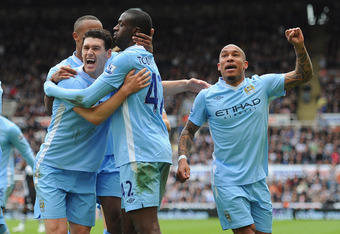 NEWCASTLE UPON TYNE, ENGLAND - MAY 06:  Yaya Toure of Manchester City celebrates scoring to make it 2-0 with team mates Nigel De Jong and Gareth Barry during the Barclays Premier League match between Newcastle United and Manchester City at the Sports Dire