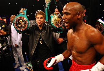 LAS VEGAS, NV - MAY 05:  (L) Singer Justin Bieber holds up a belt for Floyd Mayweather Jr. before Mayweather Jr. takes on Miguel Cotto during their WBA super welterweight title fight at the MGM Grand Garden Arena on May 5, 2012 in Las Vegas, Nevada.  (Pho