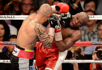 LAS VEGAS, NV - MAY 05:  Miguel Cotto (L) hits Floyd Mayweather Jr. during the ninth round of their WBA super welterweight title fight at the MGM Grand Garden Arena May 5, 2012 in Las Vegas, Nevada. Mayweather won by unanimous decision.  (Photo by Ethan M