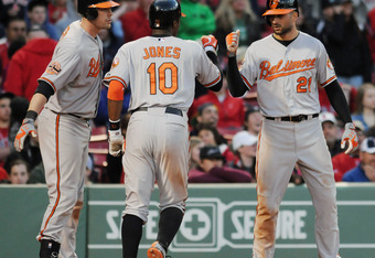 BOSTON, MA - MAY 6: Adam Jones #10 of the Baltimore Orioles is congratulated after hitting a three run homerun in the seventeenth inning by teamates Nick Markakis #21 and Matt Wieters #32 against the Boston Red Sox at Fenway Park May 6, 2012 in Boston, Ma